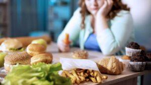 An overweight woman at table full of unhealthy food