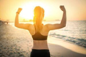 Back view of strong sporty girl showing muscles at the beach during sunset.